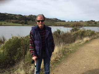 Bill wearing blue jeans, a red, black and gray flannel shirt, blue vest, sunglasses with support cane extended and long cane in pouch clipped to belt standing by lake at Grant Ranch Park with green rolling hills, trees, shrubs and a gray cloudy sky overhead